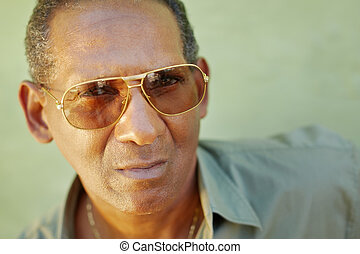serious aged man with sunglasses looking at camera -...