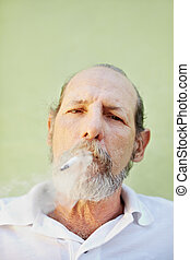 aged caucasian man smoking cigarette - portrait of mature...