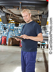 Yong mechanic with digital tablet - Portrait of young...