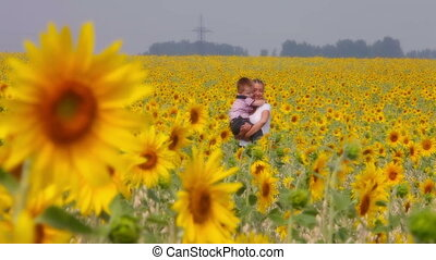Woman and child - A young woman walking among sunflowers...