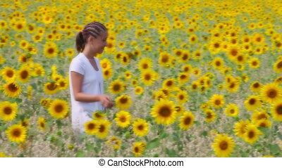 Woman in meadow - A young woman walking among sunflowers and...