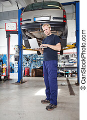 Portrait of smiling mechanic working on laptop - Full length...