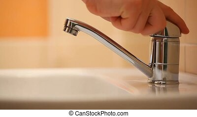 Tap water - Mans hand starting and stopping tap water in...