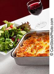baking dish with lasagna and salad