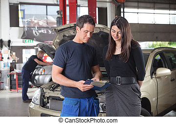 Mechanic showing the cost of service to female client while...