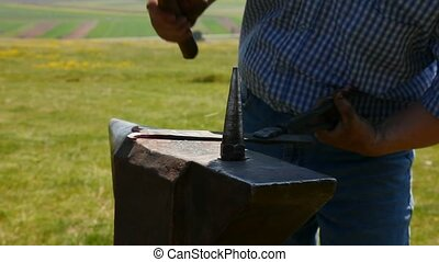 Modern smith - Smith hammering a piece of iron on anvil