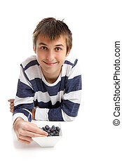 Boy eating blueberries - A young boy wearing a striped shirt...