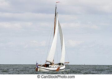 Sailing a flatbottom boat - Man sailing a wooden frisian...