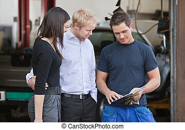 Mechanic standing with customers - Mature couple standing...