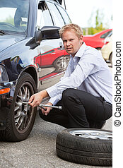 Business Man Replacing Tire - Unhappy business man replacing...