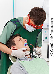 Patient visiting dentist - Young man going through therapy...