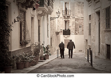 Retro photo of old narrow street of european town Valletta,...