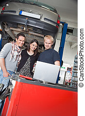 Couple standing with mechanic using laptop - Smiling young...