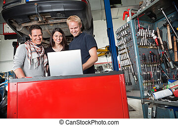 Smiling couple standing with mechanic using laptop - Young...