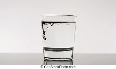 Black Ink Dropping In Glass Of Water