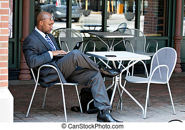 Business Man Working on His Laptop Outdoors - An African...