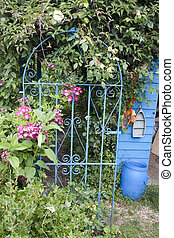 old wrought iron gate to a secret garden - blue gate in an...