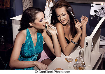 Two smiling women doing make up