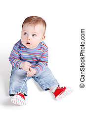 Small Child Playing With His Shoe-laces Isolated Over White