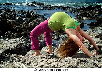 Backbend - Pregnant woman in a yoga backbend pose on a beach...