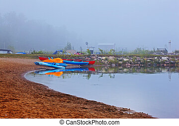 canoes and kayak in fog - canoes and kayaks in early morning...