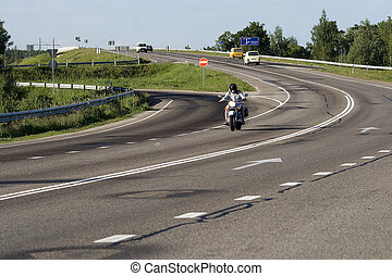 A motorcyclist going on a highway of a winding road