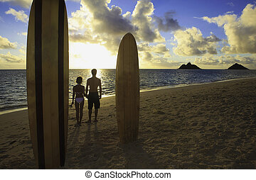 couple on the beach with their surfboards