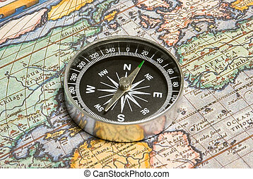 The beginning of a way - Round compass and ancient map close...