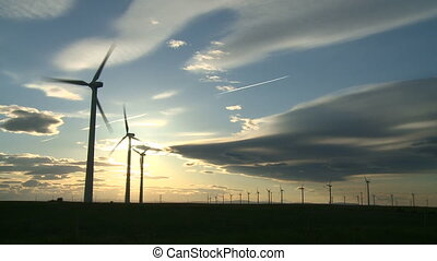 Wind Turbines - Rows of wind turbines with sun and dramatic...