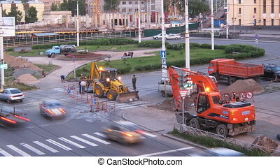 Excavator and truck working on the road