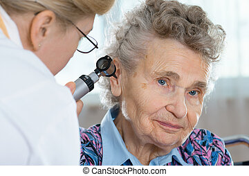 Senior woman being examined by the - Doctor performing ear...