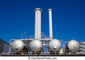 Silver tanks with smokestacks - An industrial plant with...