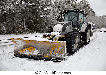 Snow Plough - A snow plough tractor with a yellow scoop on a...