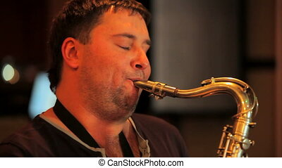 Play saxophone - The man enjoys playing the saxophone.