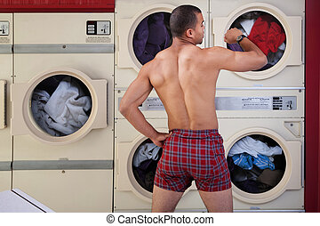 Half-naked Man in Laundromat - Muscular man in boxer shorts...