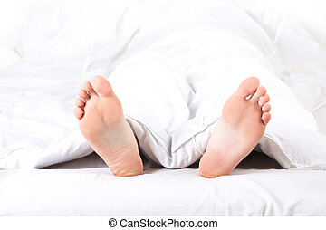 Mens feet under a white blanket