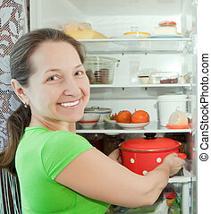 Mature woman putting pan into refrigerator at home