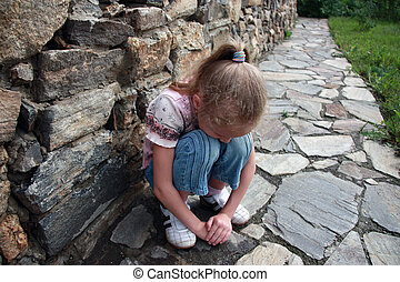 girl buried her face in her knees - sad little girl sitting...