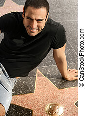 Man on walk of fame - Man smiling posing with a star on...