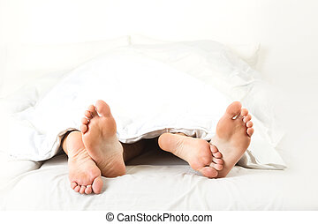 Foot of two people in the bedroom