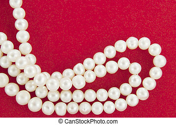 Pearl beads on red background