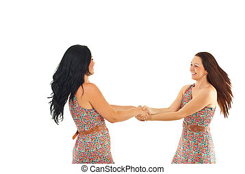 Two women twirl together - Two happy women holding hands and...