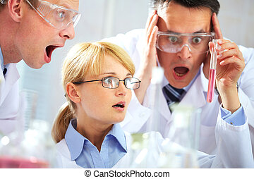 What is it - Three chemists looking shocked at a tubing and...