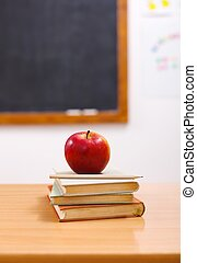 Red apple on books in class room