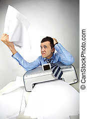 Annoyance - Portrait of nervous businessman holding printed...