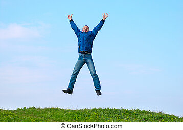 Jumping man on the hill with green grass