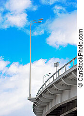 lamppost at the overpass on background of blue sky with clouds
