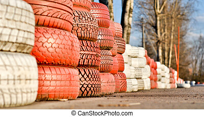 racetrack fence of white and red of old tires