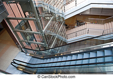 glass elevator shafts, escalators and stairs in a modern...