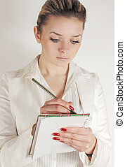 Business woman writes into the notebook the information